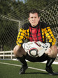 Mixed race goalkeeper crouching with soccer ball