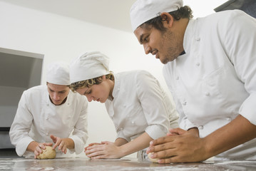 Bakers working with dough in bakery kitchen