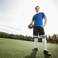 Caucasian soccer player holding ball on soccer field