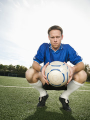 Caucasian soccer player crouching holding soccer ball