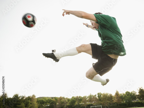 Caucasian soccer player in mid-air kicking soccer ball