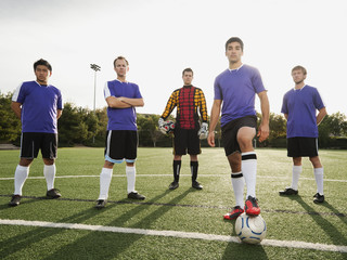 Men standing with ball on soccer field