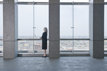 Caucasian businesswoman looking out lobby window