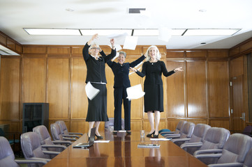 Businesswomen standing on table and throwing papers in conference room