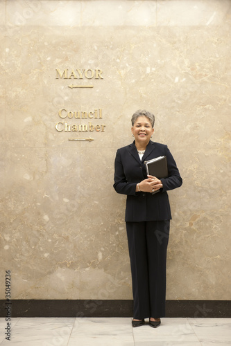 African American businesswoman standing in office corridor
