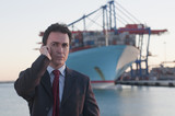 Hispanic businessman talking on cell phone with container ship in background