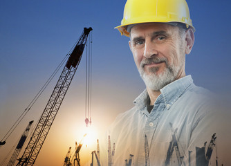 Caucasian foreman in hard-hat with cranes in background