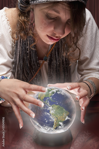 Mixed race fortune teller with crystal ball shaped like globe