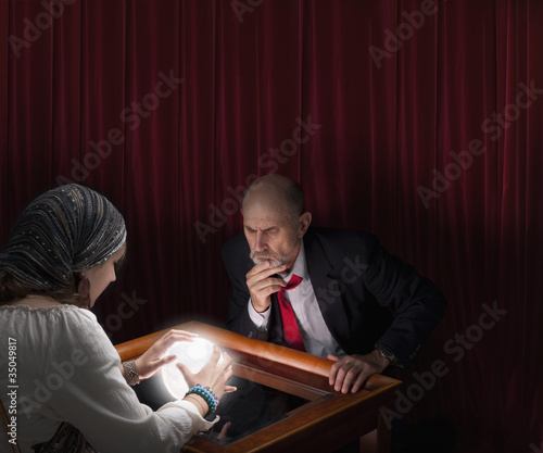 Businessman visiting fortune teller with crystal ball