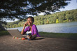 African American businesswoman sitting at picnic bench talking on cell phone