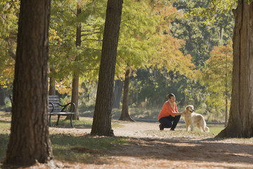 African American woman petting dog in park