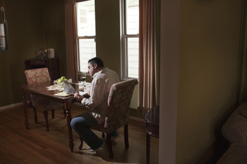 Caucasian man having dinner and reading