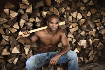 Bare chested African American man near woodpile holding ax