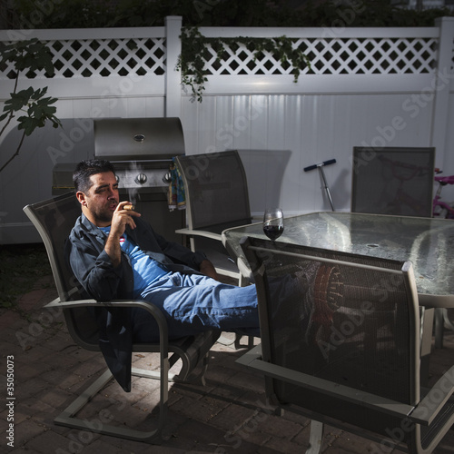 Caucasian man drinking wine and smoking on patio