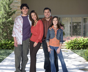 Family standing on walkway in front of house