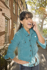 Hispanic woman talking on cell phone outdoors