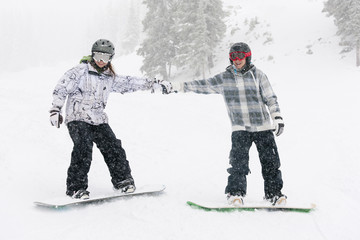 Snowboarders holding hands on ski slope
