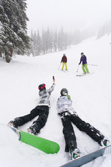 Snowboarders taking picture of skiers