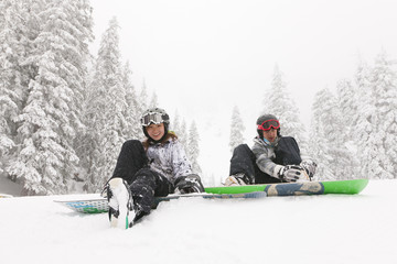 Snowboarders sitting in snow