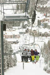 Friends riding ski lift
