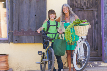 Caucasian grandmother and grandson standing with bicycles
