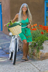 Caucasian woman pushing bicycle