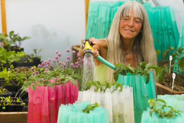 Caucasian woman watering plants in garden