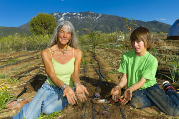 Caucasian grandmother and grandson working in garden