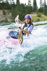 Caucasian teenager kayaking in river