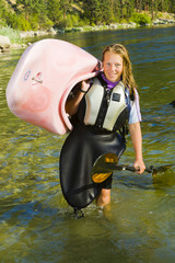 Caucasian teenager carrying kayak in river