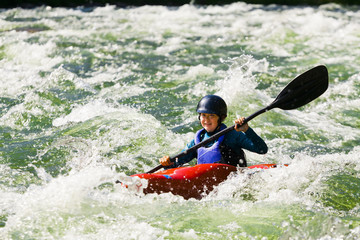 Caucasian girl kayaking in river