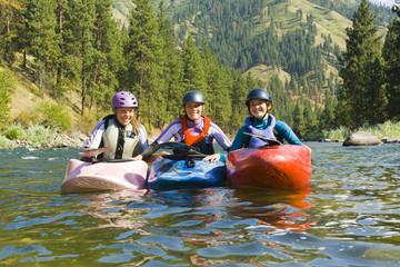 Caucasian girls kayaking in river