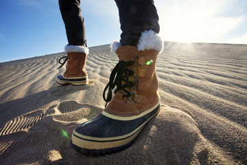 Person wearing boots standing in sand