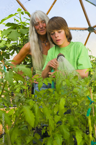 Caucasian grandmother and grandson gardening