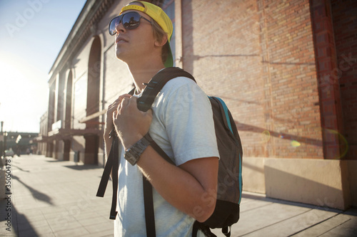 Caucasian man wearing sunglasses and backpack