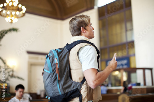 Caucasian man with backpack in train station