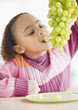 African American girl eating grapes