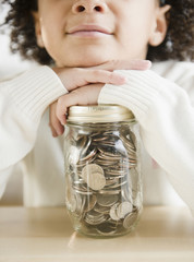 African American girl holding jar of coins