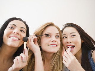 Friends putting makeup on together