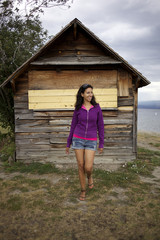 Hispanic woman standing near wooden shed
