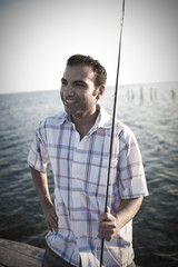 Hispanic man standing on pier with fishing rod