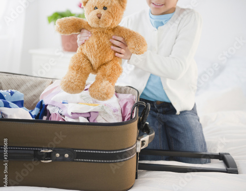 African American girl putting teddy bear in suitcase