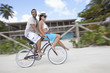 Couple riding bicycle in tropical area