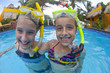 Caucasian girls snorkeling in swimming pool