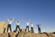 Business people standing on rocks with arms raised