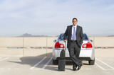 Hispanic businessman standing in parking lot with luggage
