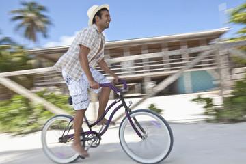 Hispanic man riding bicycle in tropical area