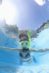 Caucasian girl snorkeling in swimming pool