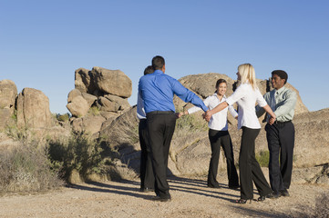 Business people holding hands in the desert