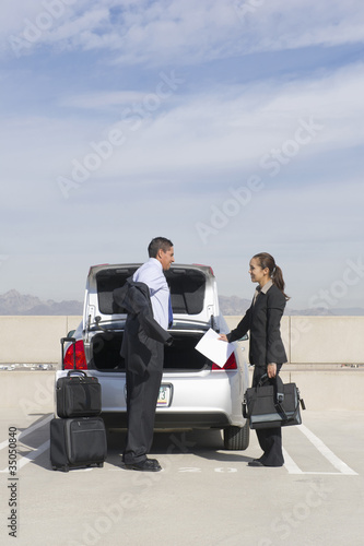 Business people unloading car in parking lot